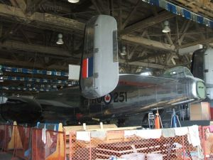 A partially restored B-25 Mitchell bomber visible in the restoration workshop.